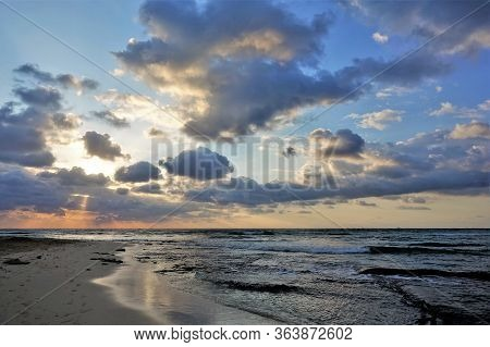 Sunrise On The Caribbean. The Rays Of The Rising Sun Break Through The Clouds And Color Them In Gold