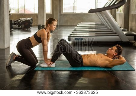 Young Fitness Couple Doing Sit Ups Together In Gym .  Fit Man And Personal Trainer Woman Assistance