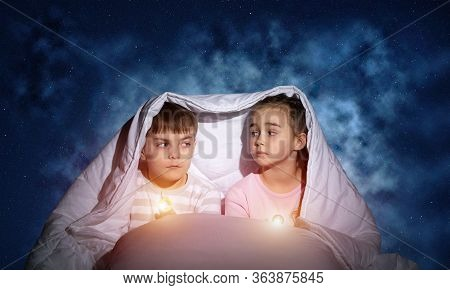 Children With Flashlights Lying In Bed. Sister And Brother Hiding Under Blanket. Covered Kids Afraid