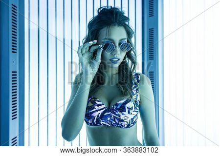 Sexy Girl Straightens Vintage Glasses In A Tanning Bed. Portrait Of A Attractive Young Woman With Ha