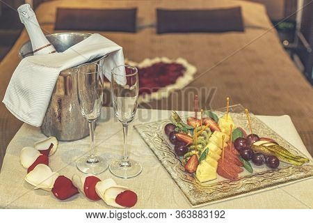 Hotel Suite For Honeymoon: Table With Champagne And Fruit Plate, In The Background A Bed Decorated W