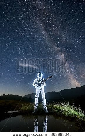 Spaceman - Guitarist Wearing Space Suit Standing At The Lake Playing Guitar At Night, Legs Reflected