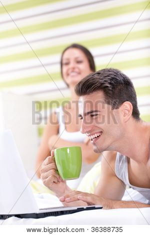 Smiling couple having fun with laptop in bedroom
