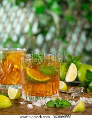 Refreshing Iced Drink With Lime, Mint And Rum Over Rustic Background With Copy Space. Refreshing Col