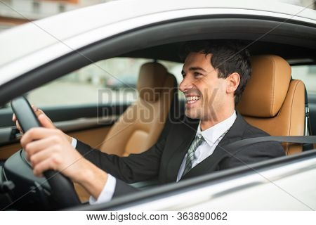 Smiling business man driving his new white car
