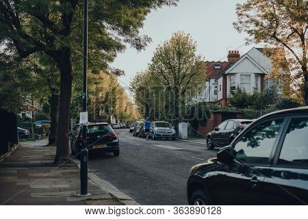 London, Uk - April 22, 2020: Man Running Past Cars Parked On A Street In Palmers Green, A Suburban A