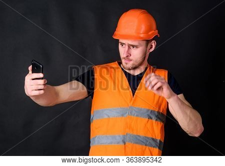 Man In Helmet, Hard Hat Taking Selfie Photo, Dark Background. Worker, Contractor, Builder On Strict