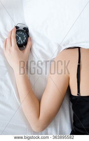 Young Woman With Pillow Over Her Head With Alarm Clock In The Hand In The Morning. Student Or School