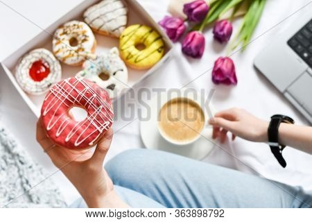 The Concept With Morning Coffee In A Romantic Style In The Bed. Purple Tulips Flowers, Box Of Donuts