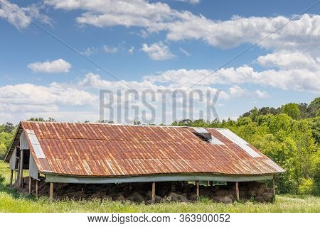 View Of A Field, Pole Barn With Rusty Tin Roof, Open Sides With Hay Bales, Idyllic Blue Sky With Clo