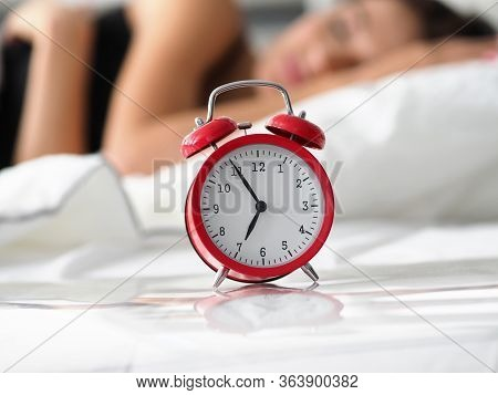 Red Old Fashioned Alarm Clock Set At Seven In Morning While Woman Sleeping At Background In Her Bed