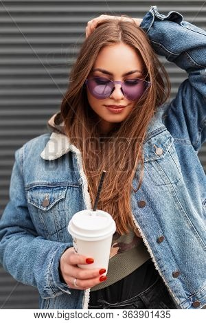 Pretty Young Hipster Woman In Stylish Glamorous Purple Glasses In Trendy Blue Denim Jacket With Coff