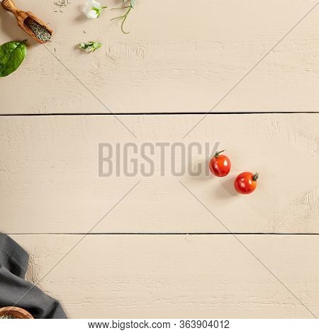 Flavoring and napkin on wooden table top view. Crumpled tablecloth, spices in wooden bowl and bucket, flower buds, greenery and tomatoes on wooden boards. Rustic style decoration, table setting