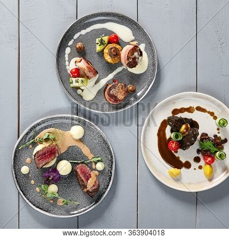 Hot meals, meat appetizers in ceramic plates top view. Veal cheeks, pork in bacon, Veal tenderloin filet mignon. Meat with vegetables and sauces. Gastronomy, served restaurant dishes on wooden table