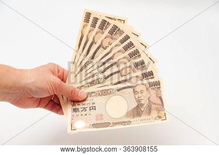 Hand Holding 100,000 Yen. Isolated On White Background. Copy Space. Horizontal Shot.