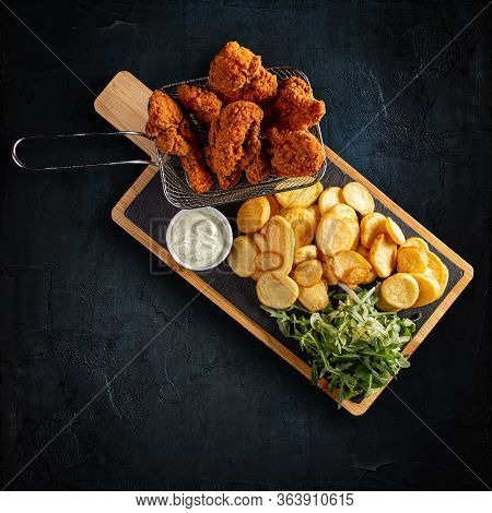 Flat Lay Of Crispy Fried Chicken Breast Strips With Golden Potatoes And Garlic Sauce On Dark Backgro