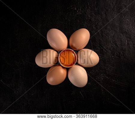 Flat Lay Of Chicken Egg Is Half Broken Among Other Eggs On Black Background