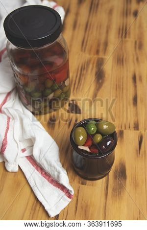 Mediterranean Olives, In A Jar, Wooden Board Background And White Cloth. Mix Of Olives In Marinade