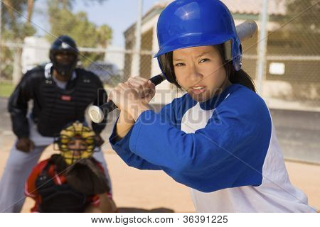 Young Asian softball player holding bat with keeper and umpire in the background