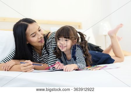 Stay Home.  Asian Girl And Mother Relax And Painting And Drawing On The White Bed At Home.  People F