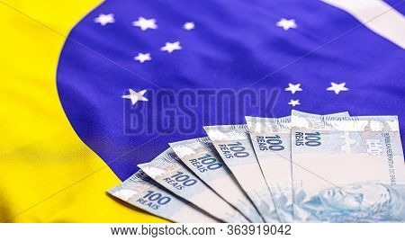 600 Brazilian Reais, Banknotes Of 100 Reais Together, With The Brazilian Flag In The Background. Con