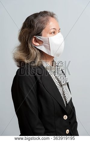 Half Body Portrait Of Middle-aged Mixed Race Woman In Formal Wear Wearing White Surgical Mask For Pr