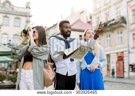 Multi-ethnic Travelers Using Local Map Together On Sunny Day, African Man Pointing Forward And Showi
