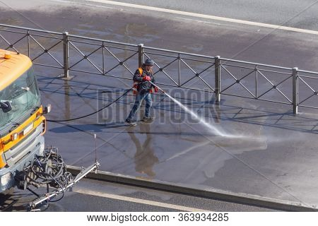 Worker Cleaning Driveway With Gasoline High Pressure Washer Splashing The Dirt, Asphalt Road. High P