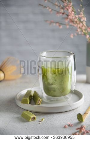 Glass Of Matcha Latte With Matcha Chocolate, Chasen Whisk On Gray Table