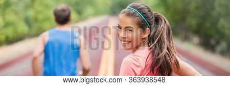 Running couple on road run in park banner panoramic header. Fit athletes runners man and woman training partners friends jogging in summer outdoors. Asian girl looking back smiling.