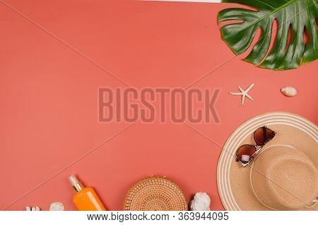 Summer Straw Hat, Tropical Monstera Leaf, Sunglasses, Shells, Suncream, Starfish On Red Background.