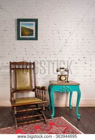 Retro Composition Of Classical Leather Rocking Chair, Wooden Green Vintage Table And Antique Golden