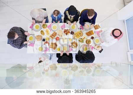 Eid Mubarak Muslim people praying before iftar dinner. Eating traditional food during Ramadan feasting month at home. The Islamic Halal Eating and Drinking at modern western Islamic family top view