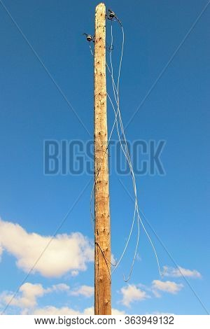 Old Wooden Pole With Broken Electric Wires. Close-up View Of Old Abandoned Wooden Pole For Fixing El