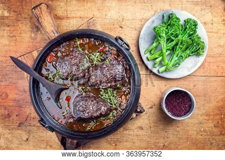 Traditional German braised beef cheeks in brown red wine sauce with carrots and broccoli offered as top view in a modern design stewpot on an old rustic board