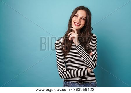 Photo of joyful nice woman in striped sweater smiling and looking upward isolated over blue wall