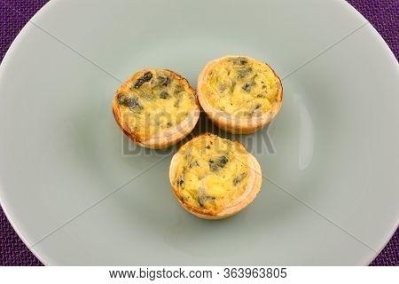 Three Mini Bite Size Spinach Florentine Quiche Pastries On Green Plate