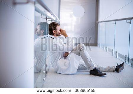 Tensed doctor sitting in corridor of hospital