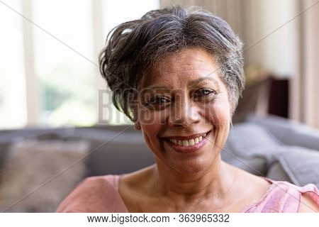 Portrait of a senior mixed race woman enjoying her time at home, sitting on a couch, looking at the camera and smiling, social distancing and self isolation in quarantine lockdown during coronavirus