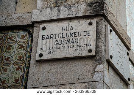 Classic Historical Street Sign On The Grey Wall Of Old Building Facade In Lisbon. Rua Bartolomeu De