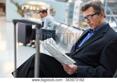 Business man as a passenger reads newspaper in airport waiting area, waiting for the flight
