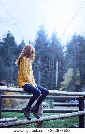 Girl Sitting On A Wooden Fence