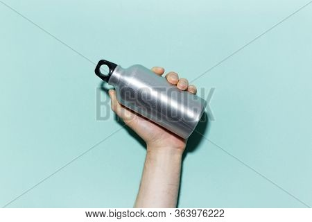 Close-up Of Male Hand Holding Reusable, Aluminum Thermo Bottle For Water, On Studio Background Of Cy