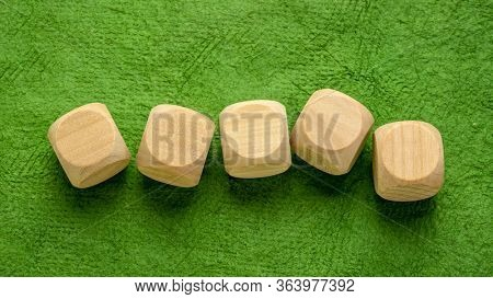 a row of blank wooden dice cubes on a green handmade bark paper, craft concept