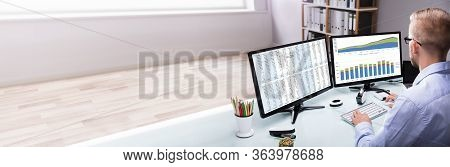 Analyst Looking At Data Table Report On Computer Desk
