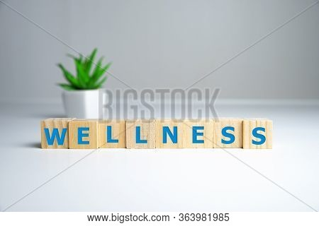 Wellness Sign With Wooden Cubes And Flowers