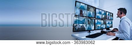 Security System Operator Looking At Cctv Camera Footage On Computer