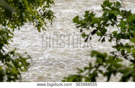 Defocused Leaves Frame The Fast Moving Flood Waters In Oklahoma After A Deluge Of Spring Rains. Boke
