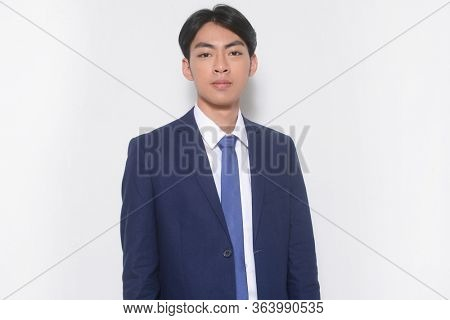 Portrait of young businessman wearing blue suit and blue tie, standing isolated on white background in studio