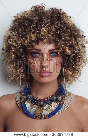 Portrait of young beautiful woman with afro hair and fancy ethnic makeup